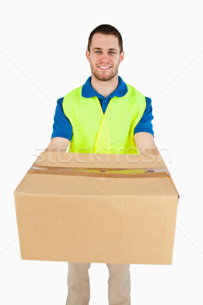 Smiling young delivery man handing over parcel against a white background Stock photo © wavebreak_media