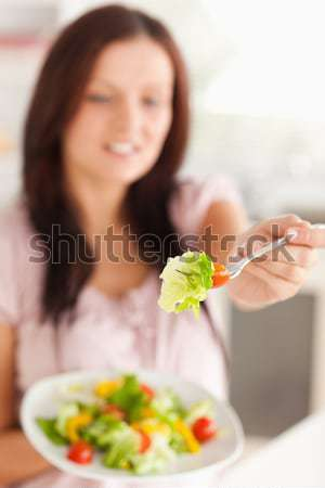 Salad offered by smiling young woman against a white background Stock photo © wavebreak_media