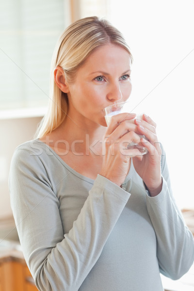 Young woman drinking a glass of water in the kitchen Stock photo © wavebreak_media