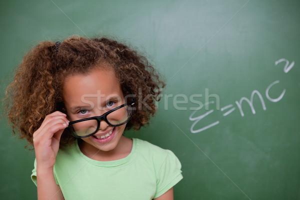 Smart schoolgirl looking above her glasses in front of a blackboard Stock photo © wavebreak_media