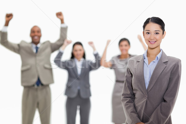 Stock photo: Close-up of a businesswoman smiling with enthusiastic co-workers raising their arms in the backgroun