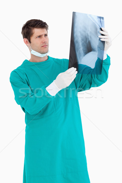 Close up of male doctor wearing scrubs looking at x-ray against a white background Stock photo © wavebreak_media