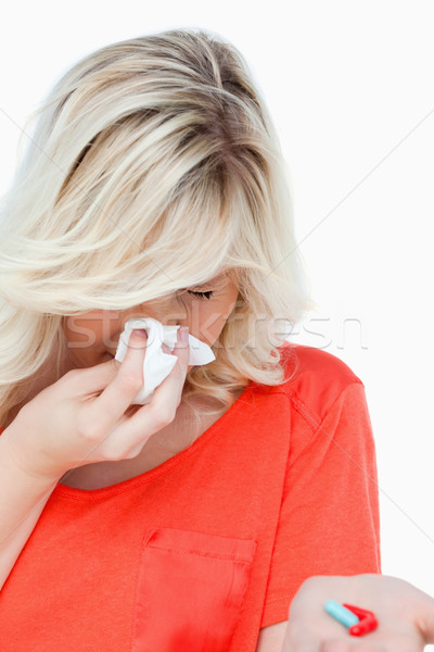 Woman sneezing while holding red and blue drugs against a white background Stock photo © wavebreak_media