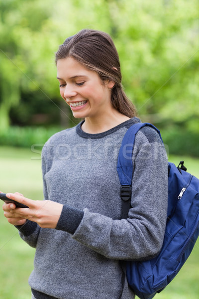 Mosolyog fiatal lány küldés szöveg mobiltelefon áll Stock fotó © wavebreak_media