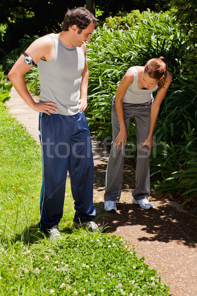 Man wearing a pedometer watching a woman as she is bent over while recovering next to bushes Stock photo © wavebreak_media