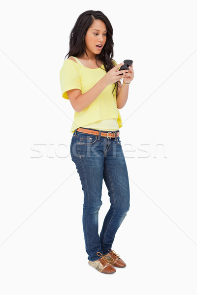 Latin student surprised while using a smartphone against white background Stock photo © wavebreak_media