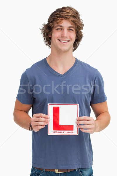 Smiling young man holding a learner driver sign against white background Stock photo © wavebreak_media