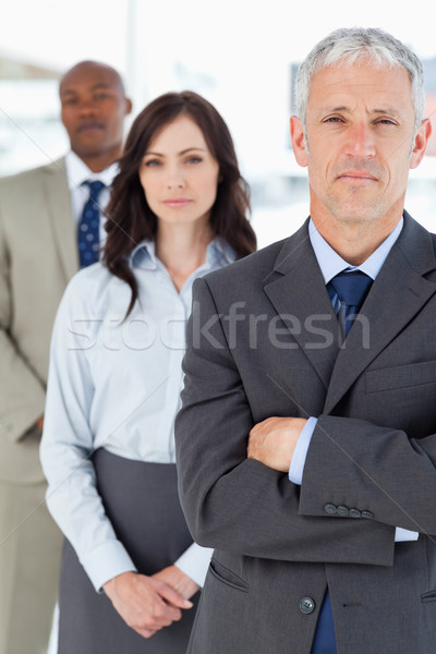 Mature manager crossing his arms in front of two young members of his team Stock photo © wavebreak_media