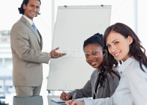 Young smiling executives sitting at the desk with a co-worker behind them Stock photo © wavebreak_media