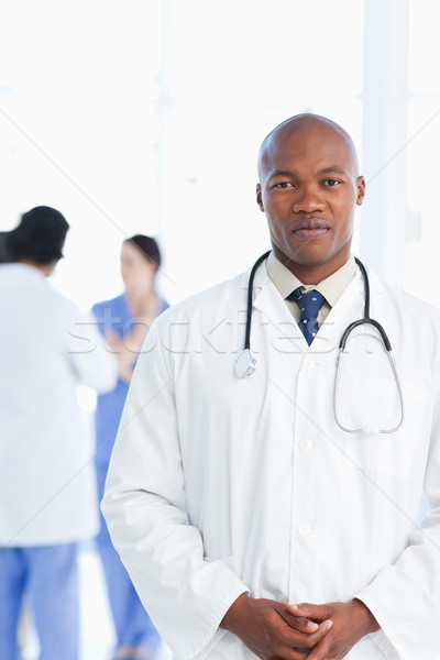 Doctor standing upright with his hands crossed with his medical team standing behind him Stock photo © wavebreak_media