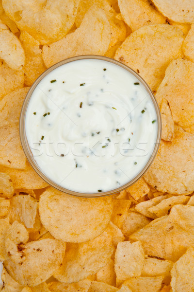 Close up of a bowl of white dip with herbs surrounded by nachos Stock photo © wavebreak_media