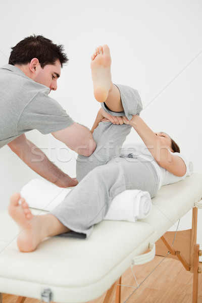 Brown-haired woman lying while stretching her leg in a room Stock photo © wavebreak_media