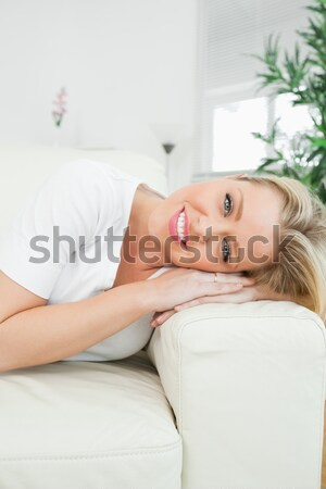 Casual woman resting with her head on the armrest of the white sofa Stock photo © wavebreak_media