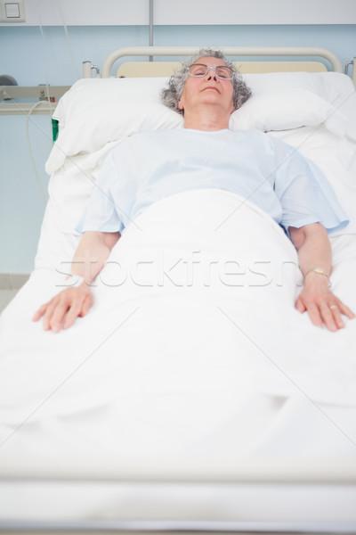 Elderly patient lying on a bed in hospital ward Stock photo © wavebreak_media