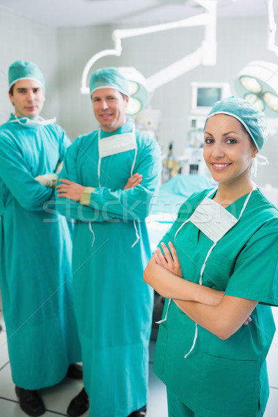 Surgical team standing up with arms crossed in an operating theatre Stock photo © wavebreak_media