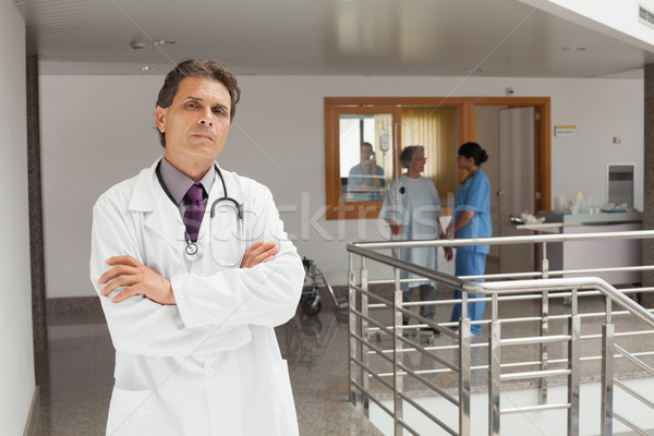 Doctor standing in the hallway while crossing his arms and looking serious Stock photo © wavebreak_media