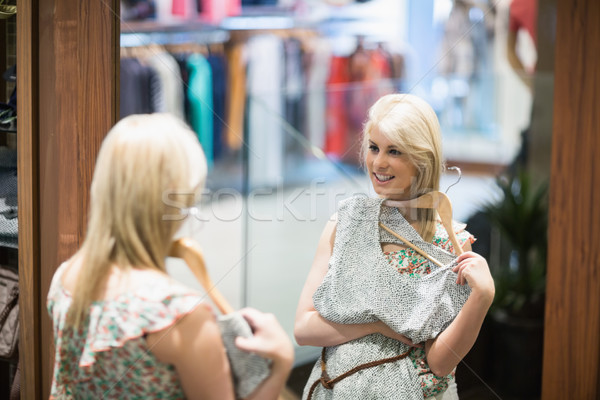 Woman is looking in the mirror at the boutique Stock photo © wavebreak_media