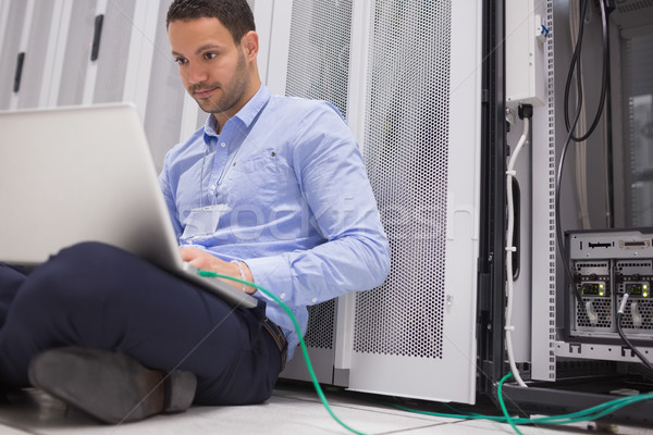 Man concentrating on laptop connected to server in data center Stock photo © wavebreak_media