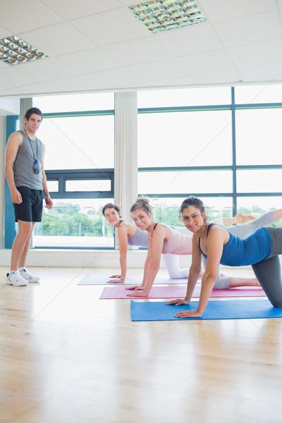 Yoga class with male instructor smiling in fitness studio Stock photo © wavebreak_media
