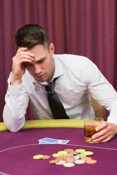 Man holding whiskey glass at poker table in casino Stock photo © wavebreak_media