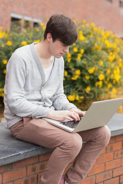Stok fotoğraf: Genç · oturma · duvar · dizüstü · bilgisayar · kullanıyorsanız · dışında · kolej