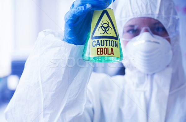Scientist in protective suit holding beaker Stock photo © wavebreak_media