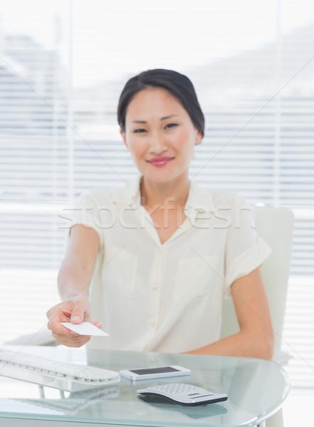 Woman handing over her business card at desk Stock photo © wavebreak_media