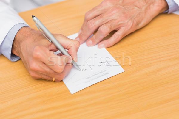 Doctor sitting at his desk writing on prescription pad Stock photo © wavebreak_media
