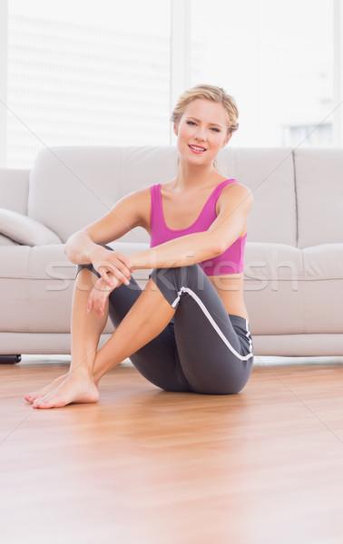 Athletic blonde sitting on floor smiling at camera Stock photo © wavebreak_media