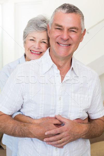 Retired couple smiling at camera and hugging Stock photo © wavebreak_media