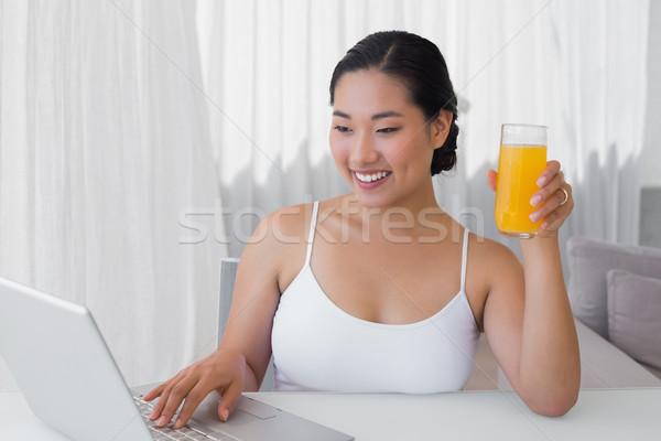 Feliz mulher usando laptop suco de laranja casa sala de estar Foto stock © wavebreak_media