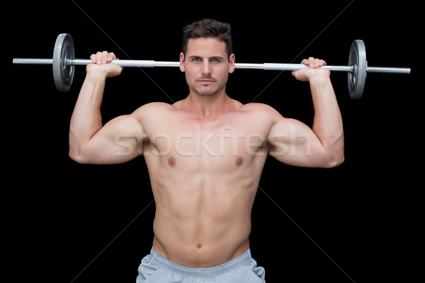 Serious handsome crossfitter lifting up barbell behind head Stock photo © wavebreak_media