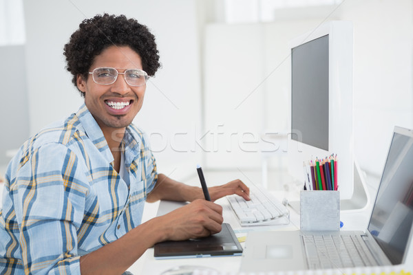 Young designer working at his desk with digitizer Stock photo © wavebreak_media