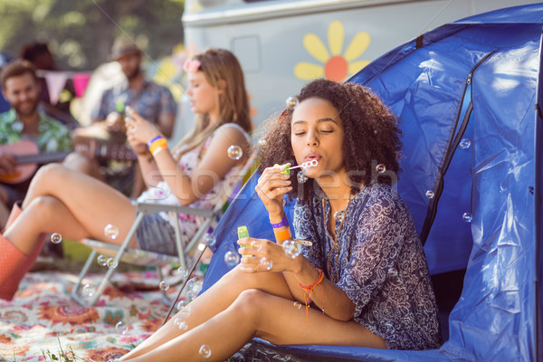 Carefree hipster blowing bubbles in tent Stock photo © wavebreak_media