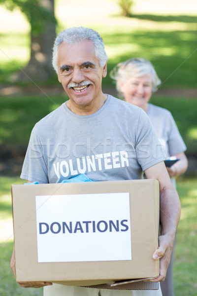 Happy volunteer senior holding donation box Stock photo © wavebreak_media