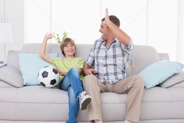 Father and son giving high-five while watching soccer match Stock photo © wavebreak_media
