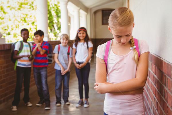 Sad schoolgirl with friends in background at school corridor Stock photo © wavebreak_media