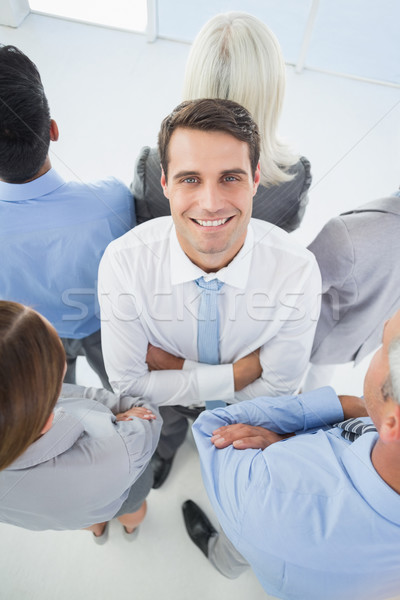 Businessman looking at camera with his colleague around him  Stock photo © wavebreak_media