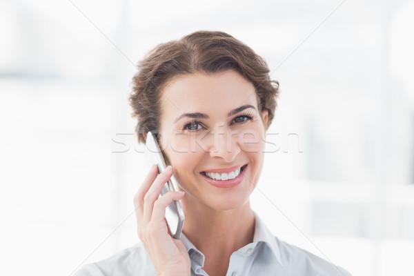 Souriant femme d'affaires téléphone regarder caméra bureau Photo stock © wavebreak_media