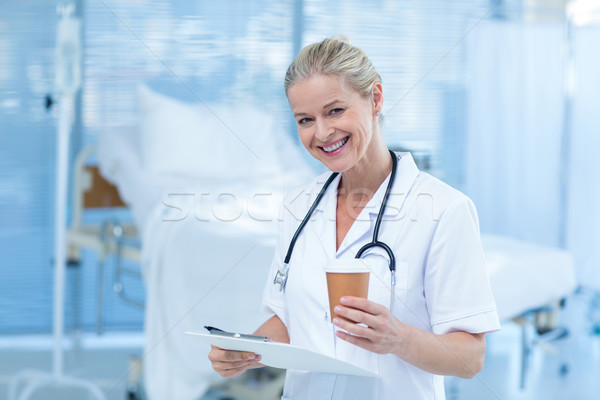 Beautiful smiling doctor holding clipboard and goblet Stock photo © wavebreak_media