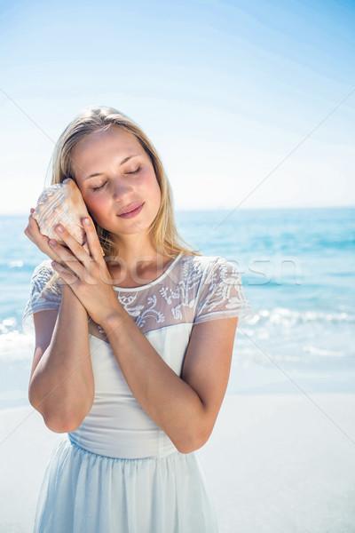 женщину прослушивании оболочки пляж рук морем Сток-фото © wavebreak_media