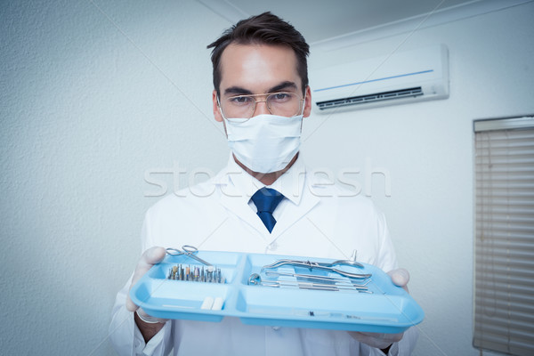 Male dentist in surgical mask holding tray of tools Stock photo © wavebreak_media