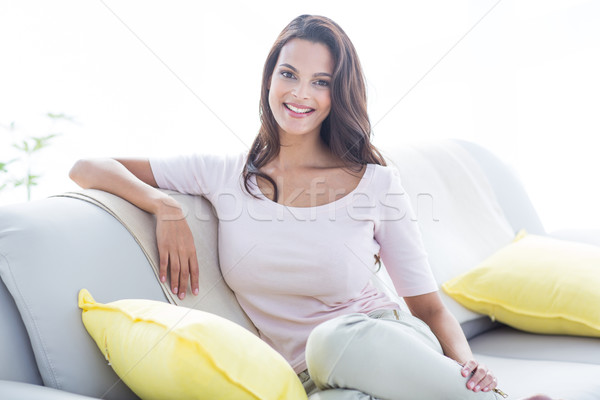 улыбаясь красивой брюнетка расслабляющая диване глядя Сток-фото © wavebreak_media