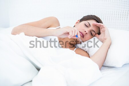 Stock photo: Sad woman looking at pills in bed
