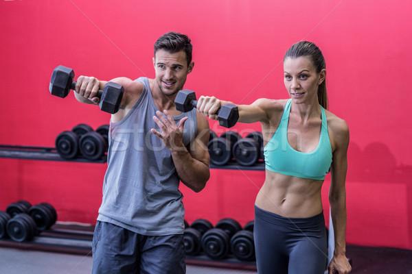 Smiling muscular couple lifting dumbbells Stock photo © wavebreak_media