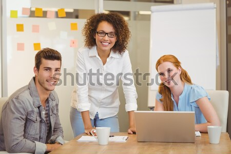 Smiling woman posing in front of her colleague with arms crossed Stock photo © wavebreak_media