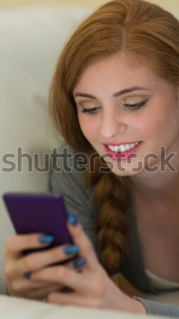 Woman holding phone with Shopping trolley icon Stock photo © wavebreak_media
