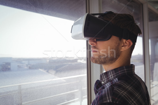 Young businessman wearing vr headset by window in office Stock photo © wavebreak_media
