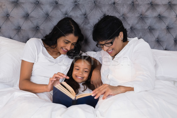 Smiling multi-generation family reading book while resting on bed Stock photo © wavebreak_media