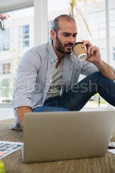 Tasarımcı tek kullanımlık fincan dizüstü bilgisayar kullanıyorsanız oturma Stok fotoğraf © wavebreak_media